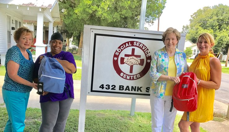 Ashley Philen (right) from Simien and Simen presents the Center with 24 back packs filled with school supplies.